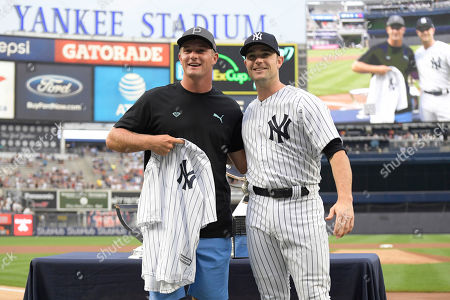 Golfer Bryson DeChambeau is presented with a jersey by New York Yankees' David Robertson before a baseball game against the Chicago White Sox, at Yankee Stadium in New York. DeChambeau won the PGA Tour's The Northern Trust 2018 on Sunday, which is the first of four events in the FedExCup Playoffs