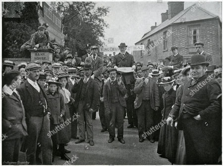 'The Chairman with the Charter'. Corby Pole Fair in Northamptonshire Taken Place Every 20 Years On Whit-monday Since 1682 in Celebration of the Charter Granted by Elizabeth I Exempting Local Landowners From Bridge Tolls Throughout the Kingdom. Photograph Showing Here of A Procession with Band at the Head and Organisers' Leaders Seated in Chairs Attached to Poles Which Are Borne On the Shoulders of Some of the Men. . Photograph by Benjamin Stone in 'Sir Benjamin Stone's Pictures', Page 2