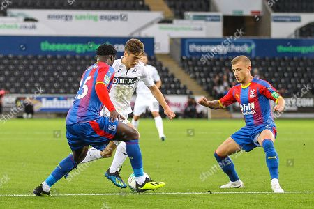Daniel James of Swansea City takes on Jeffrey Schlupp and Max Meyer of Crystal Palace