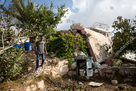 A Palestinian man inspects the house of Muhammad Dar Yusuf after it was demolished by Israeli army, in the West Bank village of Kauber near City of Ramallah, . The Israeli military says forces demolished the home of a Palestinian who killed an Israeli in a West Bank settlement last month