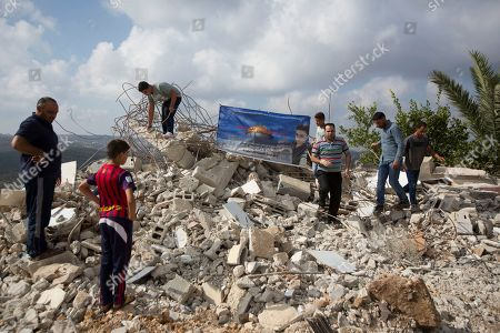 Palestinians inspect a destroyed house of Muhammad Dar Yusuf, seen on the poster, after it was demolished by Israeli army, in the West Bank village of Kauber near City of Ramallah, . Israeli forces demolish the home of a Palestinian who killed an Israeli in a West Bank settlement last month