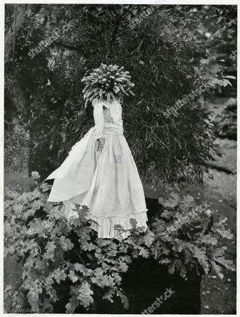 One of the Customs of the Festival of Ceres Observed in the Northern Part of Northumberland at the Close of the Reaping not the Ingathering. Immediately the Sickle Was Laid Down and the Last Sheaf Set On the End the Men Shouted That They Had 'Got the Kern'. Then A Curious Image Was Produced an Imae Dressed in A White Frock with Coloured Ribbons and Crowned with Corn Ears Stuck On A Pole and Held Aloft by the Strongest Man of the Party While the Rest Circled Round It. Photograph by Benjamin Stone in 'Sir Benjamin Stone's Pictures', Page 22