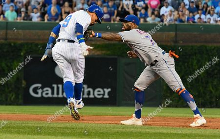 Javier Baez, Jose Reyes. Chicago Cubs' Javier Baez (9) is picked off stealing second base by New York Mets shortstop Jose Reyes (7) during the first inning of a baseball game, in Chicago