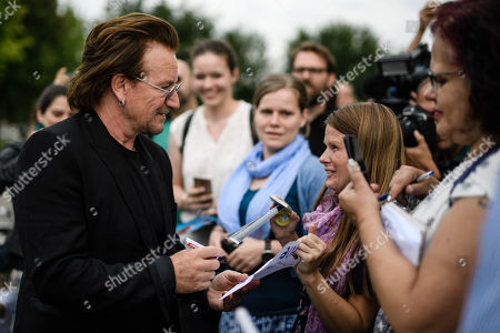 The singer of the Irish rock group U2 and co-founder of the campaign organization ONE, Paul David Hewson aka Bono Vox (L), talks to fans after a visit to German Chancellor Angela Merkel (not in the picture), in front of the chancellery in Berlin, Germany, 28 August 2018. Bono met German Chancellor Angela Merkel prior to her Africa visit for a talk.
