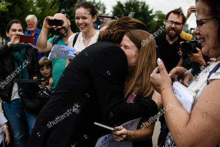 The singer of the Irish rock group U2 and co-founder of the campaign organization ONE, Paul David Hewson aka Bono Vox (C), hugs a fan after a visit to German Chancellor Angela Merkel (not in the picture), in front of the chancellery in Berlin, Germany, 28 August 2018. Bono met German Chancellor Angela Merkel prior to her Africa visit for a talk.
