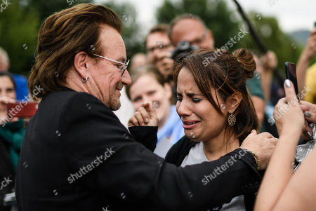 The singer of the Irish rock group U2 and co-founder of the campaign organization ONE, Paul David Hewson aka Bono Vox (L), hugs a fan after a visit to German Chancellor Angela Merkel (not in the picture), in front of the chancellery in Berlin, Germany, 28 August 2018. Bono met German Chancellor Angela Merkel prior to her Africa visit for a talk.