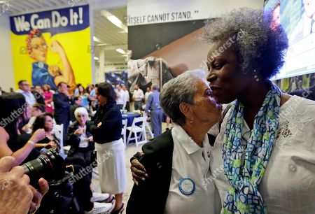 Diane Ziman, the mother of Democratic gubernatorial candidate Philip Levine, left, hugs Carmen Morris, right, during a watch party, in Miami. Levine conceded the race