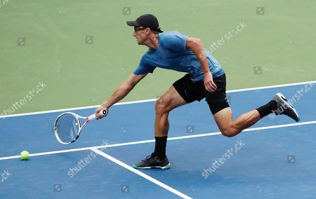 Peter Polansky, of Canada, chases down a show by Alexander Zverev, of Germany, during the first round of the U.S. Open tennis tournament, in New York