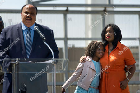 Martin Luther King, III, left, gives a speech at the U.S.-Mexico border fence, background, as his wife Arndrea Waters King and their daughter, Yolanda Renee King, 10, hug each other during a visit to the border, in San Diego, California, USA, on 28 August 2018. King, who is the son of the late civil rights leader, Martin Luther King, Jr., gave a speech calling for support of immigrant rights and separated undocumented families detained at the border. His speech was given on the 55th anniversary of his father's seminal 'I Have a Dream' speech.