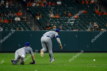 Stock Photo of Toronto Blue Jays left fielder Billy McKinney, left, and third baseman Aledmys Diaz fall as they try to catch a foul pop-up that was hit by Baltimore Orioles' Chris Davis in the eighth inning of a baseball game, in Baltimore