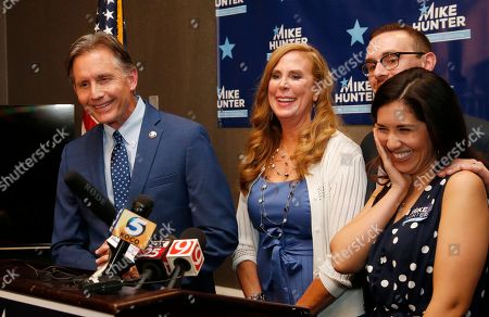 Mike Hunter, Cheryl Hunter, Barrett Hunter, Rachel Hunter. Mike Hunter, left, smiles as he answers a question from the media in the Republican primary runoff election for Attorney General in Oklahoma City, in Oklahoma City, . At right are family members, his wife, Cheryl Hunter, son Barrett Hunter, and daughter-in-law Rachel Hunter