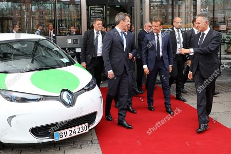 French President Emmanuel Macron (C), Crown Prince Frederik of Denmark (L) and French Ambassador to Denmark Francois Zimeray (R) walk past a electric car by French manufacturer Renault as they leave the Confederation of Danish Industry (DI) headquarters on August 29, 2018 in Copenhagen.