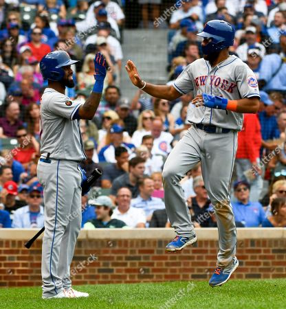 New York Mets' Amed Rosario, right, high-fives Jose Reyes, left, after he scored against the Chicago Cubs during the seventh inning of a baseball game, in Chicago