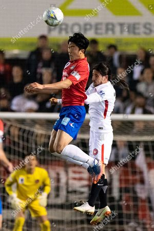 Bonnyrigg White Eagles midfielder Mun-Soo Gil (18) and Western Sydney Wanderers defender Raul Llorente (24) go up for the ball