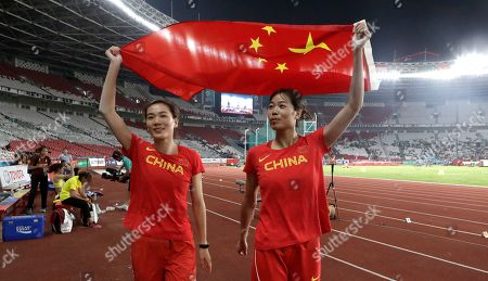 Stock Picture of China's Xu Xialing and Lu Minjia hold their national flag after the women's long jump final during the athletics competition at the 18th Asian Games in Jakarta, Indonesia. Crowds have been sparse at some Asian Games venues, particularly track and field where about 5,000 have been packed into a cordoned off section of the 76,000-seat national stadium