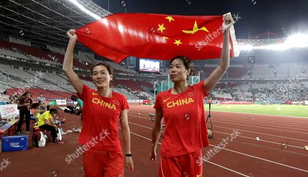 China's Xu Xialing and Lu Minjia hold their national flag after the women's long jump final during the athletics competition at the 18th Asian Games in Jakarta, Indonesia. Crowds have been sparse at some Asian Games venues, particularly track and field where about 5,000 have been packed into a cordoned off section of the 76,000-seat national stadium