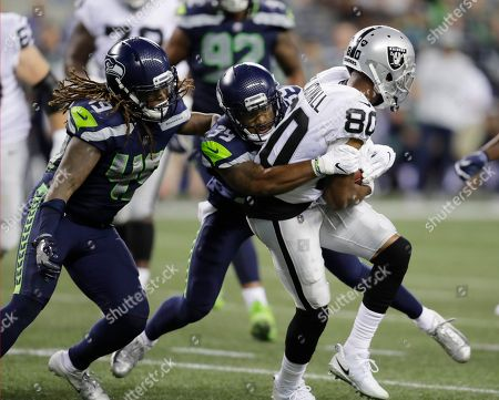 Seattle Seahawks linebacker Shaquem Griffin, left, and defensive back Dontae Johnson (39) tackle Oakland Raiders wide receiver Saeed Blacknall (80) during the first half of an NFL football preseason game