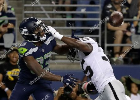 Seattle Seahawks wide receiver David Moore, left, eyes the ball after Oakland Raiders defensive back Shareece Wright, right, broke up the pass but was called for pass interference, during the first half of an NFL football preseason game