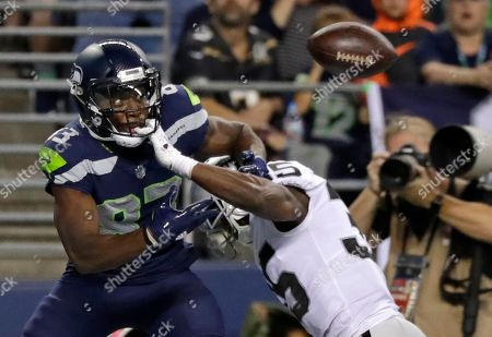 Seattle Seahawks wide receiver David Moore, left, eyes the ball after Oakland Raiders defensive back Shareece Wright, right, broke up the pass during the first half of an NFL football preseason game. Wright was called for pass interference