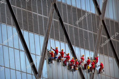 Window washers dangle from ropes as they clean the facade of the China Central Television (CCTV) headquarters building in Beijing, . The 44-story, Rem Koolhaas-designed cantilever building was completed in 2012