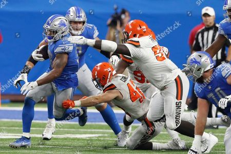 Stock Image of Dwayne Washington, Jeremy Faulk, Justin Currie. Cleveland Browns linebacker Justin Currie (42) and defensive tackle Jeremy Faulk (97) reach in to stop Detroit Lions running back Dwayne Washington during the second half of an NFL football preseason game, in Detroit