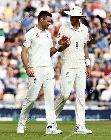 James Anderson and Stuart Broad of England look at the ball.