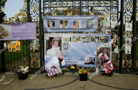 "On the 21st anniversary of the death of Britain's Diana, Princess of Wales, royal fans Joseph Afrane, left, aged 55 from London, and John Loughrey, aged 63 from London, place flowers beside the gates of her residence Kensington Palace in London, . Diana's life was cut short in a 1997 car crash in Paris, but her legend lives on and the woman then-Prime Minister Tony Blair dubbed ""the People's Princess"" still retains a loyal following"