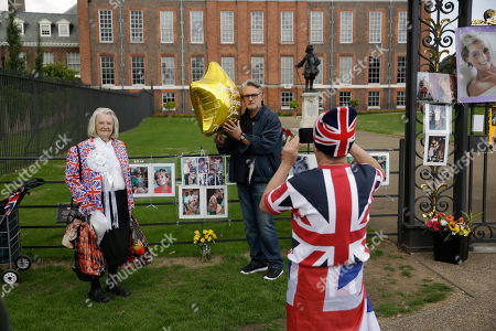 "On the 21st anniversary of the death of Britain's Diana, Princess of Wales, royal fan John Loughrey, right, aged 63 from London, takes a picture for a man who met Diana and came to pay his respects, flanked by royal fan Margaret Tyler beside the gates of Diana's residence Kensington Palace in London, . Diana's life was cut short in a 1997 car crash in Paris, but her legend lives on and the woman then-Prime Minister Tony Blair dubbed ""the People's Princess"" still retains a loyal following"