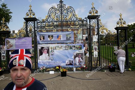 "On the 21st anniversary of the death of Britain's Diana, Princess of Wales, royal fan John Loughrey, aged 63 from London, who said he'd been there since 5am, stands in front of tributes including large posters he'd put up on the gates of her residence Kensington Palace in London, . Diana's life was cut short in a 1997 car crash in Paris, but her legend lives on and the woman then-Prime Minister Tony Blair dubbed ""the People's Princess"" still retains a loyal following"