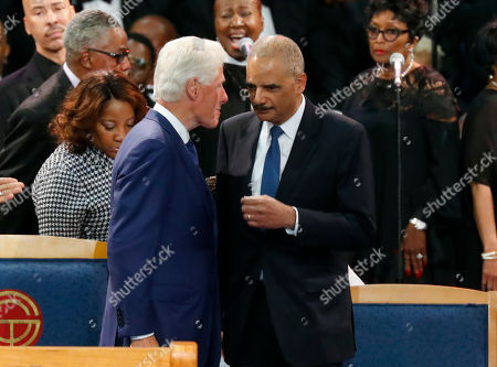 Former President Bill Clinton talks with former U.S. Attorney General Eric Holder, right, at the start of the funeral service for Aretha Franklin at Greater Grace Temple, in Detroit. Franklin died Aug. 16, 2018 of pancreatic cancer at the age of 76