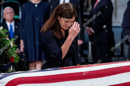 Stock Image of Former New Hampshire Senator Kelly Ayotte stands over the casket of Senator John McCain, R-Ariz., as he lies in state in the Rotunda of the U.S. Capitol,, in Washington.