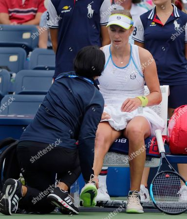 Ekaterina Makarova, of Russia, is seen by a trainer during the third round of the U.S. Open tennis tournament against Anastasija Sevastova, of Latvia, in New York