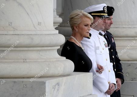 (L-R) Cindy McCain, Jack McCain, and Jimmy McCain watch as a military honor guard team carries the casket of the late Senator John McCain (R-AZ), into the U.S. Capitol, in Washington, DC.