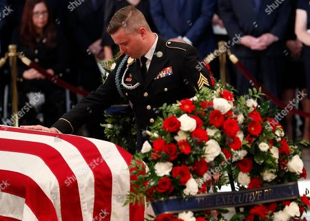 Jimmy McCain, son of late U.S. Senator John McCain, touches his father's casket during ceremonies honoring Senator McCain inside the U.S. Capitol Rotunda in Washington