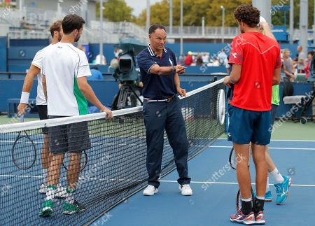 Chair Umpire Mohamed Lahyani tosses the coin before a doubles match between Robin Haase and Matwe Middelkoop, of the Netherlands, and Philipp Petzschner and Tim Puetz, of Germany, during the U.S. Open tennis tournament, in New York