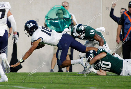 Stock Picture of Utah State quarterback Jordan Love, left, is tripped by Michigan State's Matt Morrissey (10) and Josh Butler (19) during the second quarter of an NCAA college football game, in East Lansing, Mich