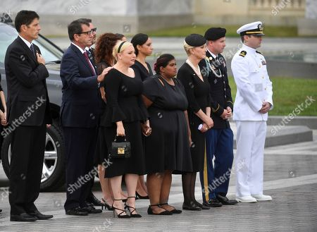 The family of Sen. John McCain, R-Ariz., including from left, Andrew McCain, Doug McCain, second from left, Meghan McCain, from front row left, Bridget McCain, Cindy McCain, Jimmy McCain and Jack McCain, watch as the casket is carried down the steps of the U.S. Capitol in Washington, in Washington, for a departure to the Washington National Cathedral for a memorial service