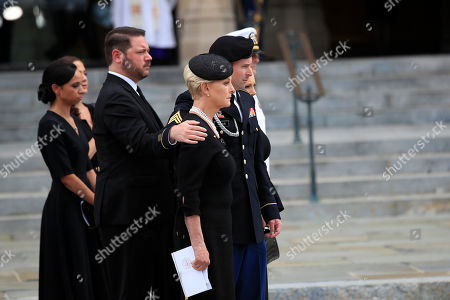 Jimmy McCain puts his arm around his mother Cindy McCain, and as other family members watch as McCain's casket is taken from the cathedral following a memorial service for Sen. John McCain, R-Ariz., at the Washington National Cathedral in Washington