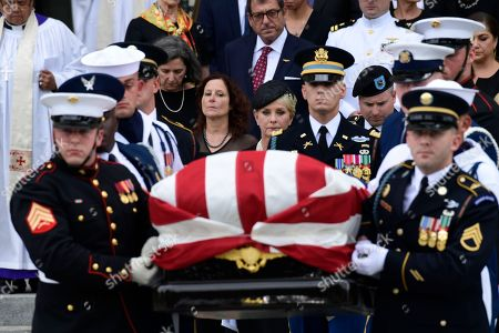 The casket of Sen. John McCain, R-Ariz., is carried out of the Washington National Cathedral in Washington, after a memorial service, as Cindy McCain is escorted by her son Jimmy McCain and other family members