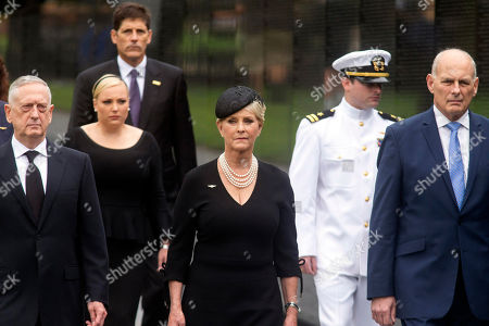 Cindy McCain, the wife of Sen. John McCain, R-Ariz., and her family, with Defense Secretary James Mattis, left, and White House Chief of Staff John Kelly, walks at the Vietnam Veterans Memorial in Washington