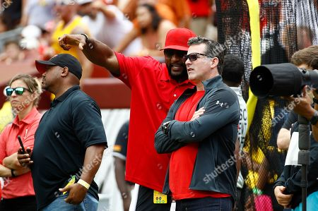 Former Baltimore Raven Ray Lewis, center, left, speaks with Under Armour CEO Kevin Plank on the Maryland sideline in the first half of an NCAA college football game between Maryland and Texas, in Landover, Md