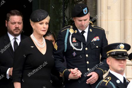 Stock Image of Cindy McCain and Jimmy McCain follow a Military Honor Guard carrying the casket of late Senator John McCain, Republican of Arizona, after a funeral service at the National Cathedral in Washington, DC.