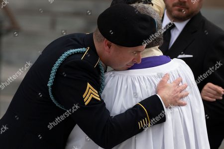 Stock Photo of Son of late Arizona Republican Senator John McCain, Jimmy McCain hugs a clergy member after a funeral service at the National Cathedral in Washington, DC.