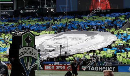 The face of Seattle Sounders forward Clint Dempsey is shown on a tifo display in the supporters section, during a pre-match ceremony in Dempsey's honor in Seattle after he announced his retirement from professional soccer earlier in the week