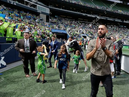 Seattle Sounders forward Clint Dempsey, right, walks off the field in front of supporters, following a pre-match ceremony in his honor in Seattle after he announced his retirement from professional soccer earlier in the week