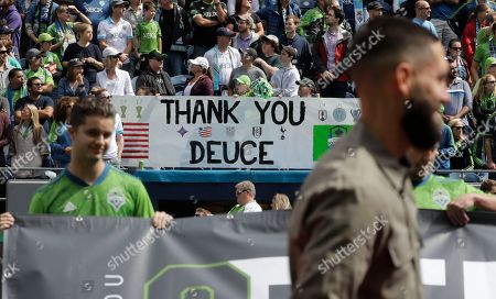 """Supporters hold a sign that reads """"Thank You Deuce"""" as Seattle Sounders forward Clint Dempsey, right, watches video tributes to him, in Seattle, during a pre-match ceremony in his honor after he announced his retirement from professional soccer earlier in the week"""