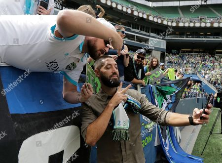 Seattle Sounders forward Clint Dempsey takes a photo with a supporter, in Seattle, following a pre-match ceremony in his honor after he announced his retirement from professional soccer earlier in the week