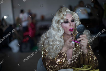 Stock Picture of Sherry Vine applies lipstick backstage ahead of performing during Wigstock, in New York. The 1980s festival, an impromptu creation of unruly patrons in drag who stumbled out of an East Village club at about 2 a.m. to improvise for homeless people in garbage-strewn, rat-infested Tompkins Square Park, was revived at New York City's Pier 17