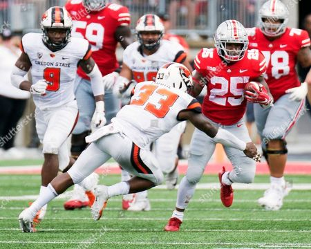 Ohio State Buckeyes running back Mike Weber (25) goes one on one with Oregon State Beavers safety Jalen Moore (33) at the NCAA football game between the Oregon State Beavers & Ohio State Buckeyes at Ohio Stadium in Columbus, Ohio