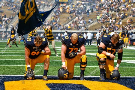 Stock Picture of California Golden Bears linebacker Evan Weaver (89), California Golden Bears linebacker Matthew Cindric (73), and California Golden Bears linebacker Nick Henderson (57) take a knee before the NCAA football game between the University of North Carolina Tar Heels and the University of California Berkeley Golden Bears at California Memorial Stadium in Berkeley, California
